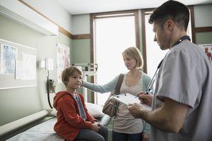 Male nurse talking to boy in examination room