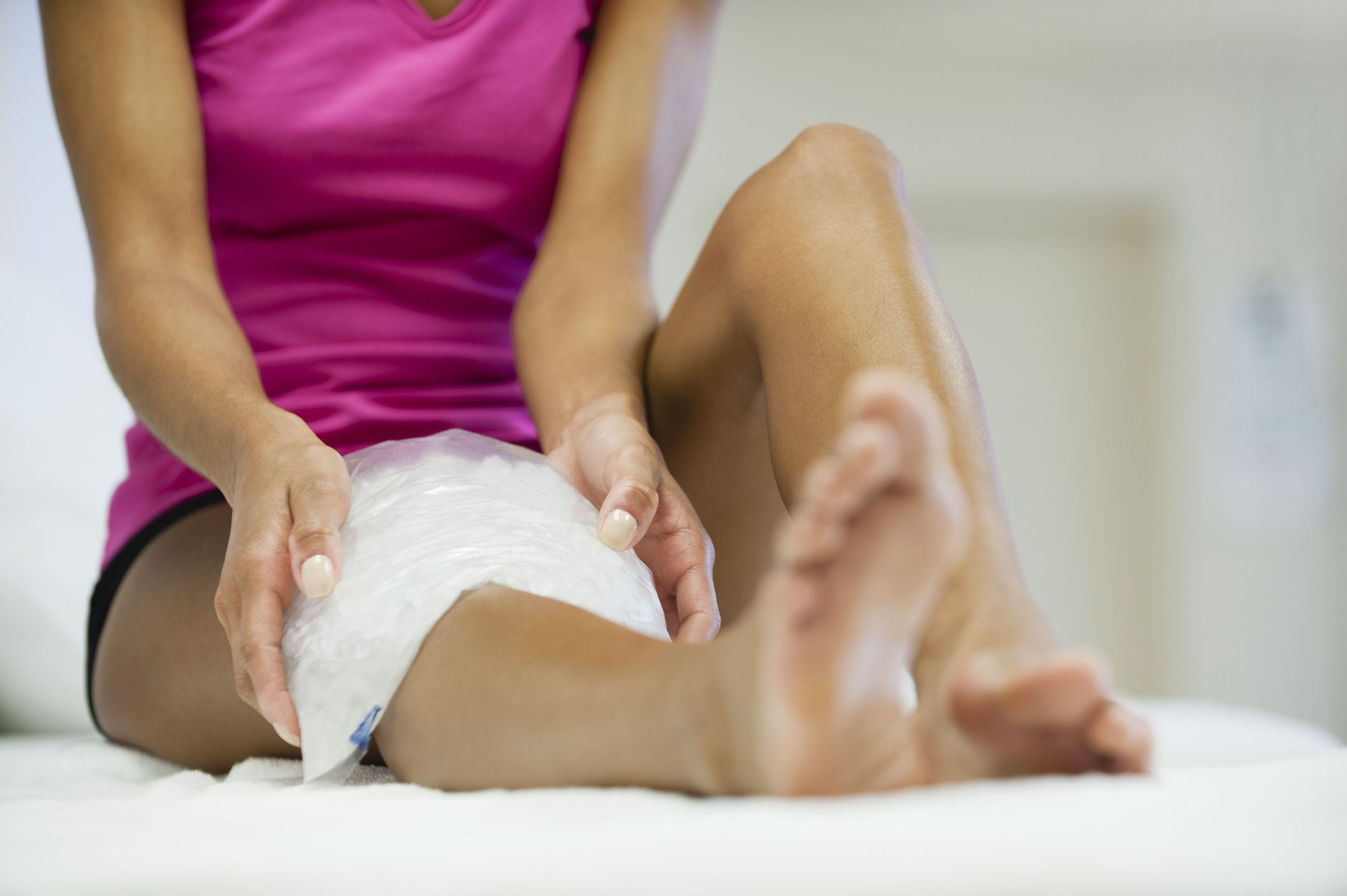 Woman icing her knee with an ice pack