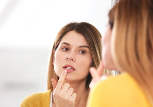 Woman applying cold sore cream on lips in front of mirror