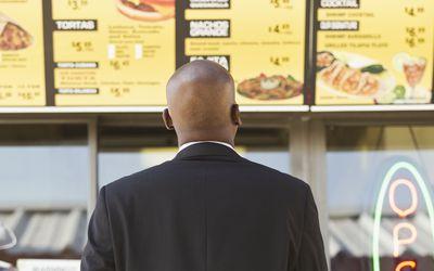 man looking at a cafe menu board