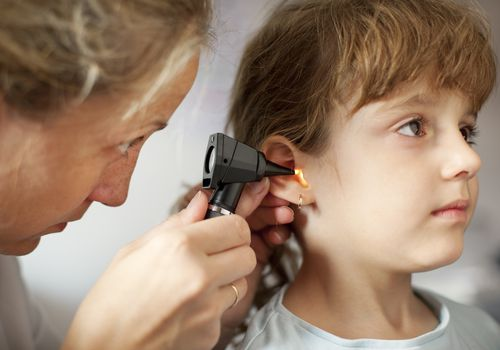 Young girl gets ear exam from pediatrician