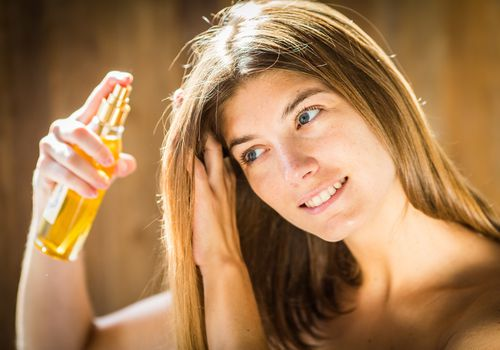 Woman applying hair oil