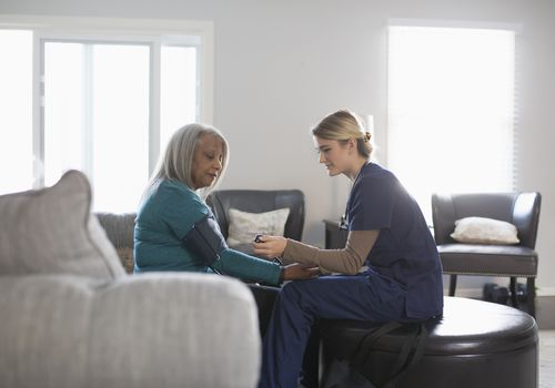 Nurse taking woman's blood pressure at home