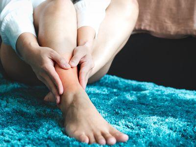 woman touching painful leg