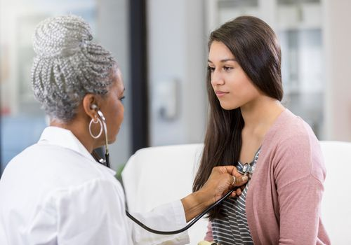 Young Hispanic woman having her heart listened to by an older Black female doctor using a stethoscope.