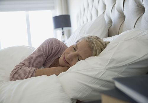 Comfortable woman sleeping in bed in wicking pajamas