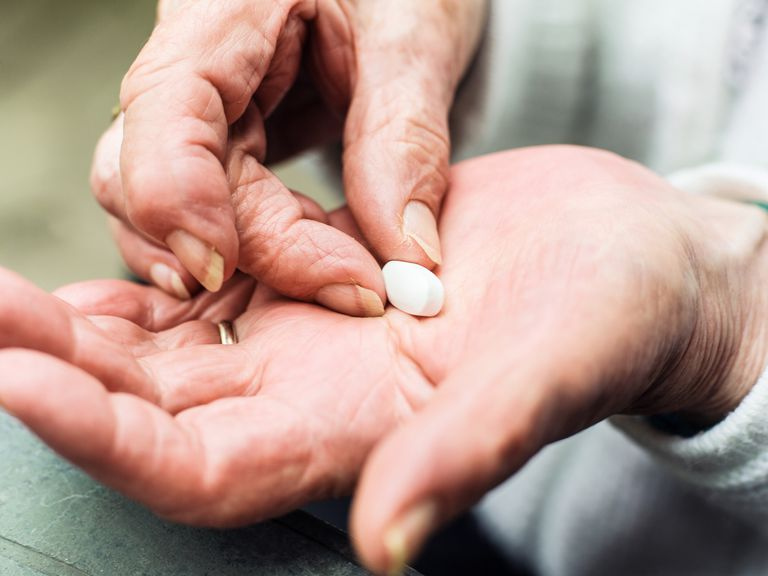 pill in elderly person's hand