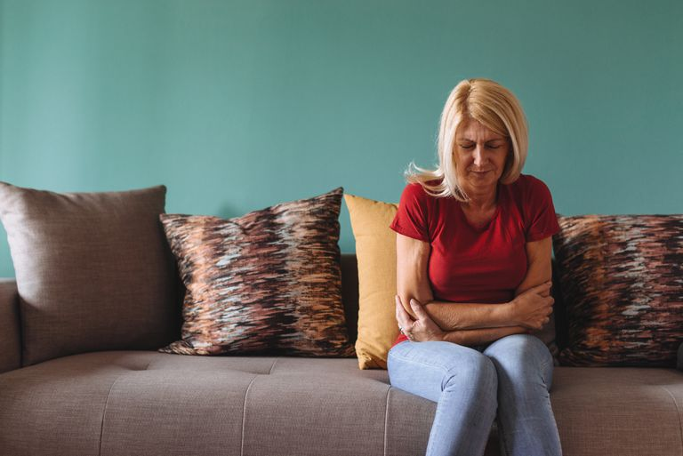Mature woman facing pelvic pain at home