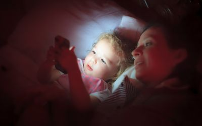 Mom and daughter playing on cell phone in bed at night