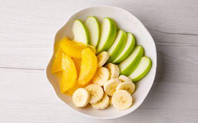 Bowl of sliced banana, orange, and apple