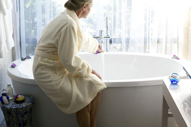 Woman, aged 59, running a bath in front of a large window.