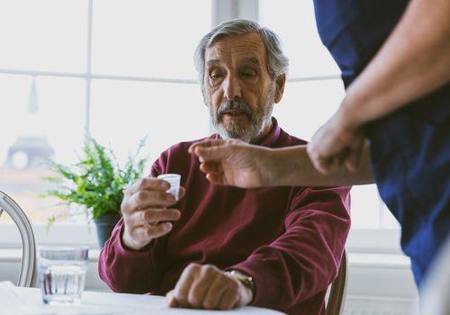 Caregiver giving medicine to senior man at home