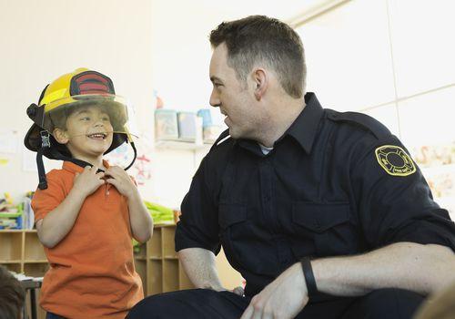 Smiling boy wearing helmet with firefighter in school