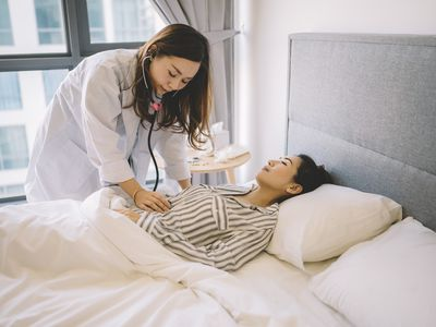 A doctor examining her patient during a home visit
