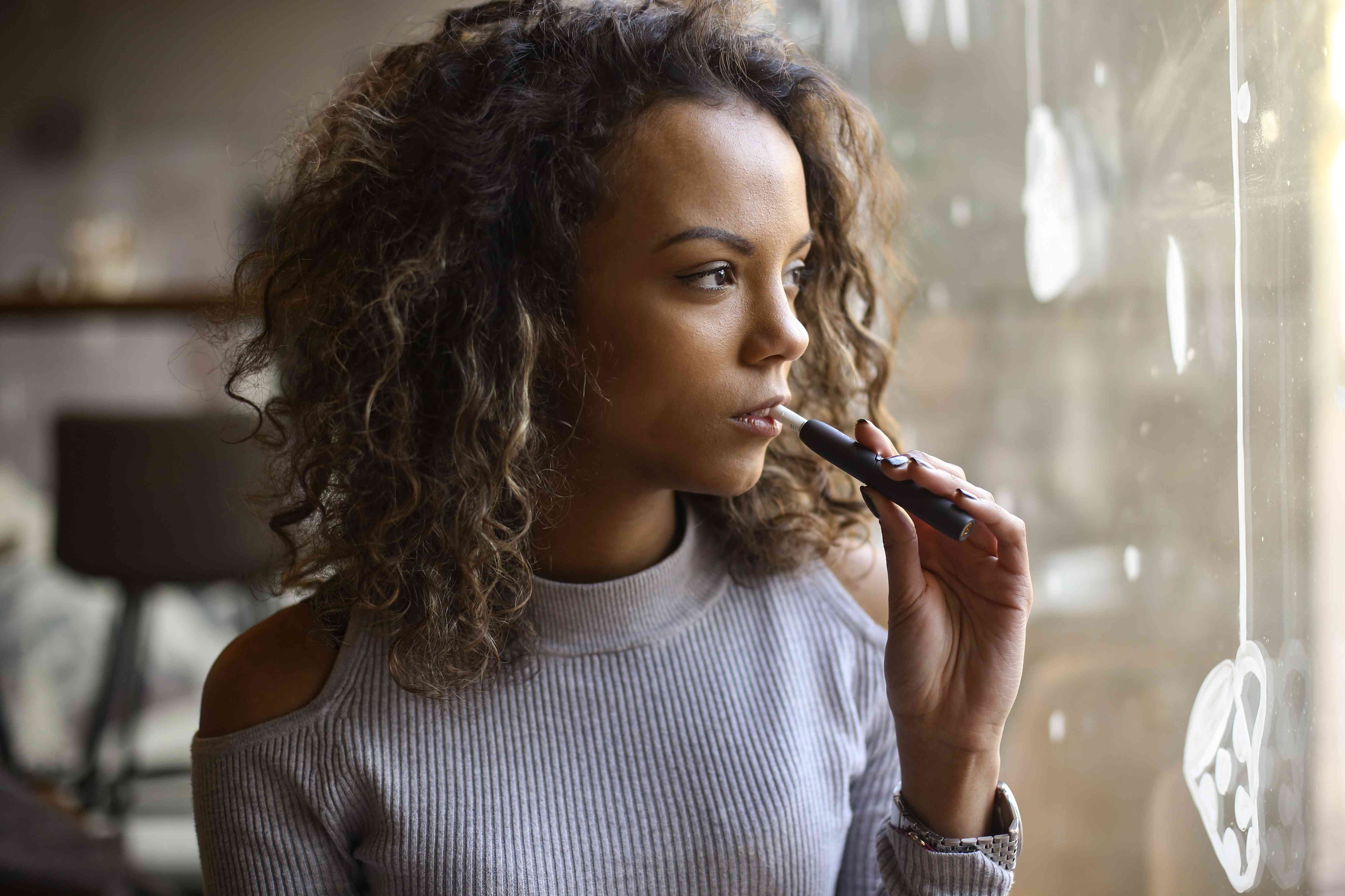 Young woman vaping in a bar