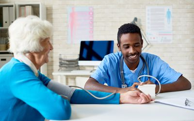 Healthcare provider taking blood pressure