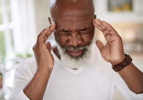 Shot of a mature man suffering from a headache at home