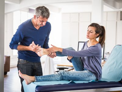 Photo of a man examining a woman's ankle.