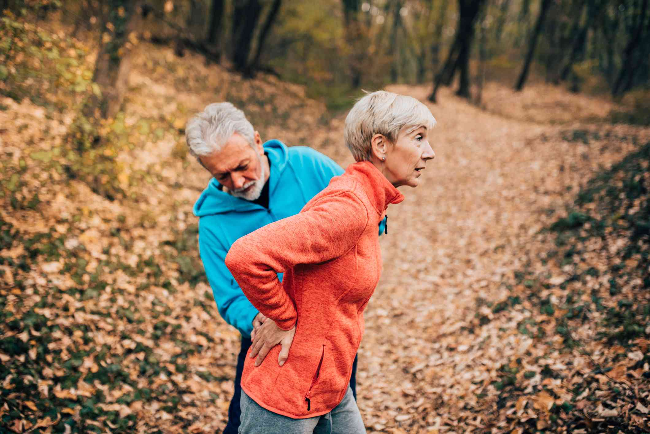 older couple exercising in the woods with back pain