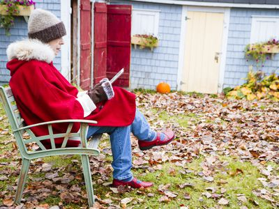 Woman reading outside during Autumn