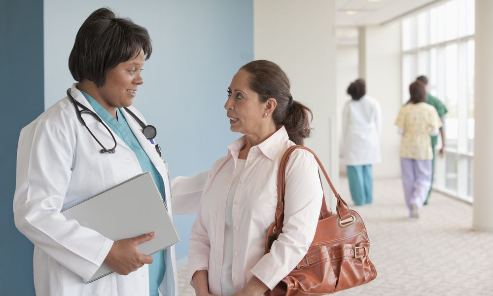 Doctors talking to woman in hospital