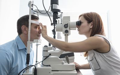 Optician looking into patients eyes at small business opticians