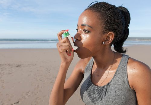 young jogger using asthma inhaler on the beach.