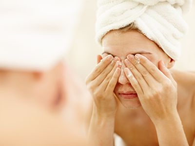 Woman with towel wrapped around her head cleans eye area