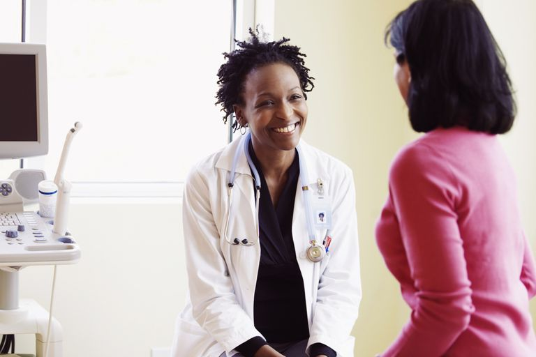 Woman talking to female doctor in exam room