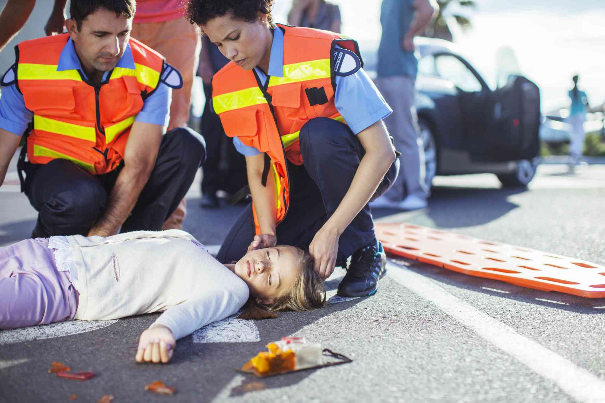 First responders checking an unconscious girl