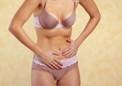 Woman in underwear with stomach pain