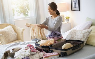 Mixed race woman packing suitcase in bed