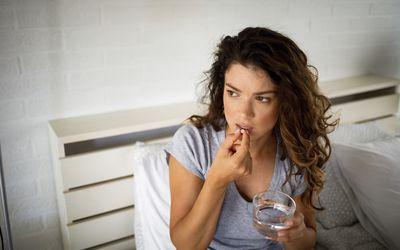 A young woman sitting on her bed at home and taking pills with water - stock photo