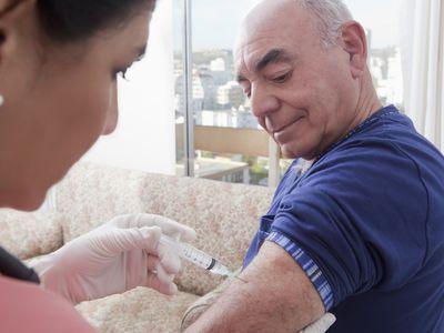 Nurse giving older man a vaccine