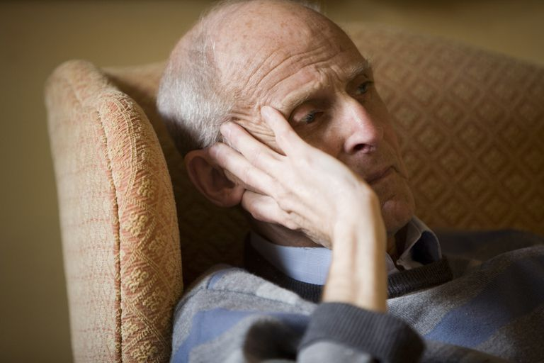 A man with dementia sadly sits in his chair