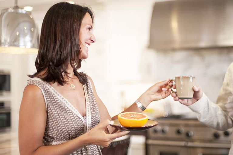 Woman holding half a grapefruit on a plate and accepting a cup of coffee