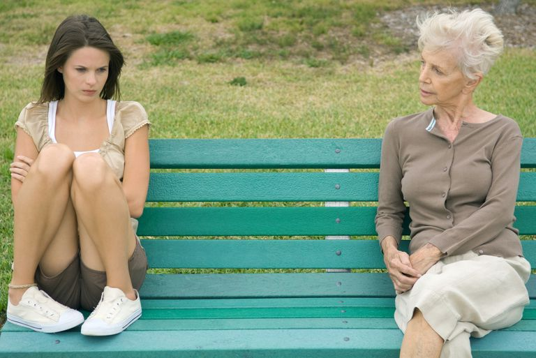 Teenage girl sitting apart from grandmother on bench, arms folded
