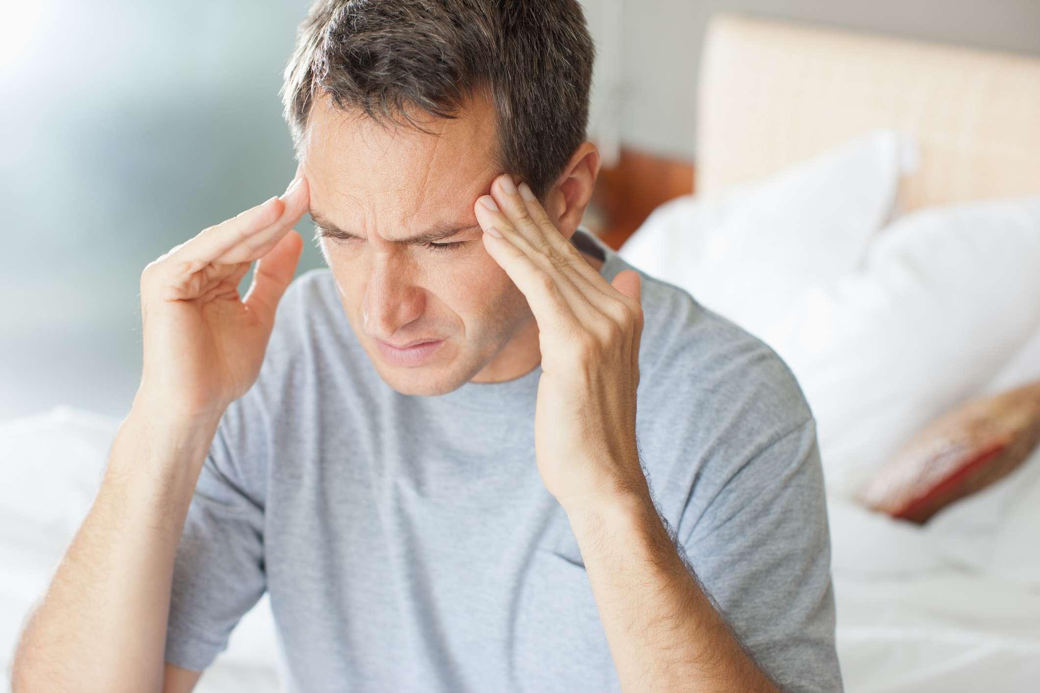 Man rubbing in his head while having a headache