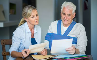 senior man with broken shoulder in sling reviewing files with woman