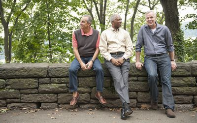 Older men sitting on stone wall in park