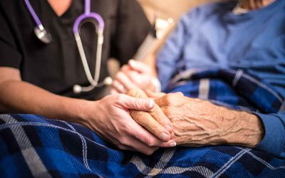 a nurse holds the hands of an elderly patient