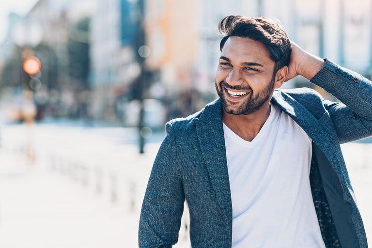 Smiling man walking down the street running a hand through his hair