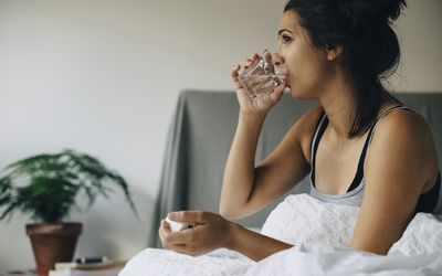 Women in bed in the morning drinking water