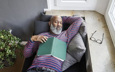 Mature man lying on bench with a book, taking a nap