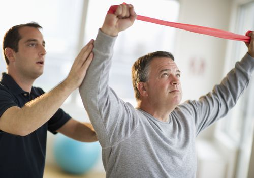 man using exercise band during rotator cuff rehab