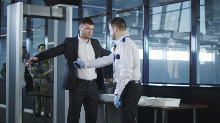 Security agent using a metal detector on a man