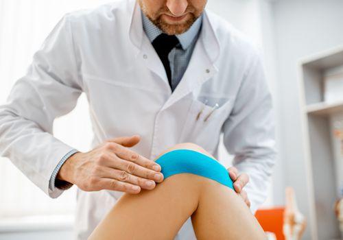 Doctor using kinesiology tape on knee