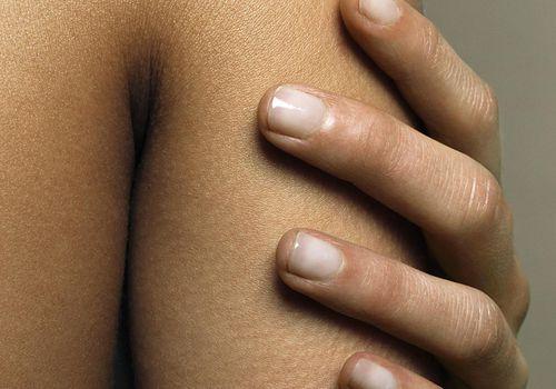 Woman touching arm, close-up