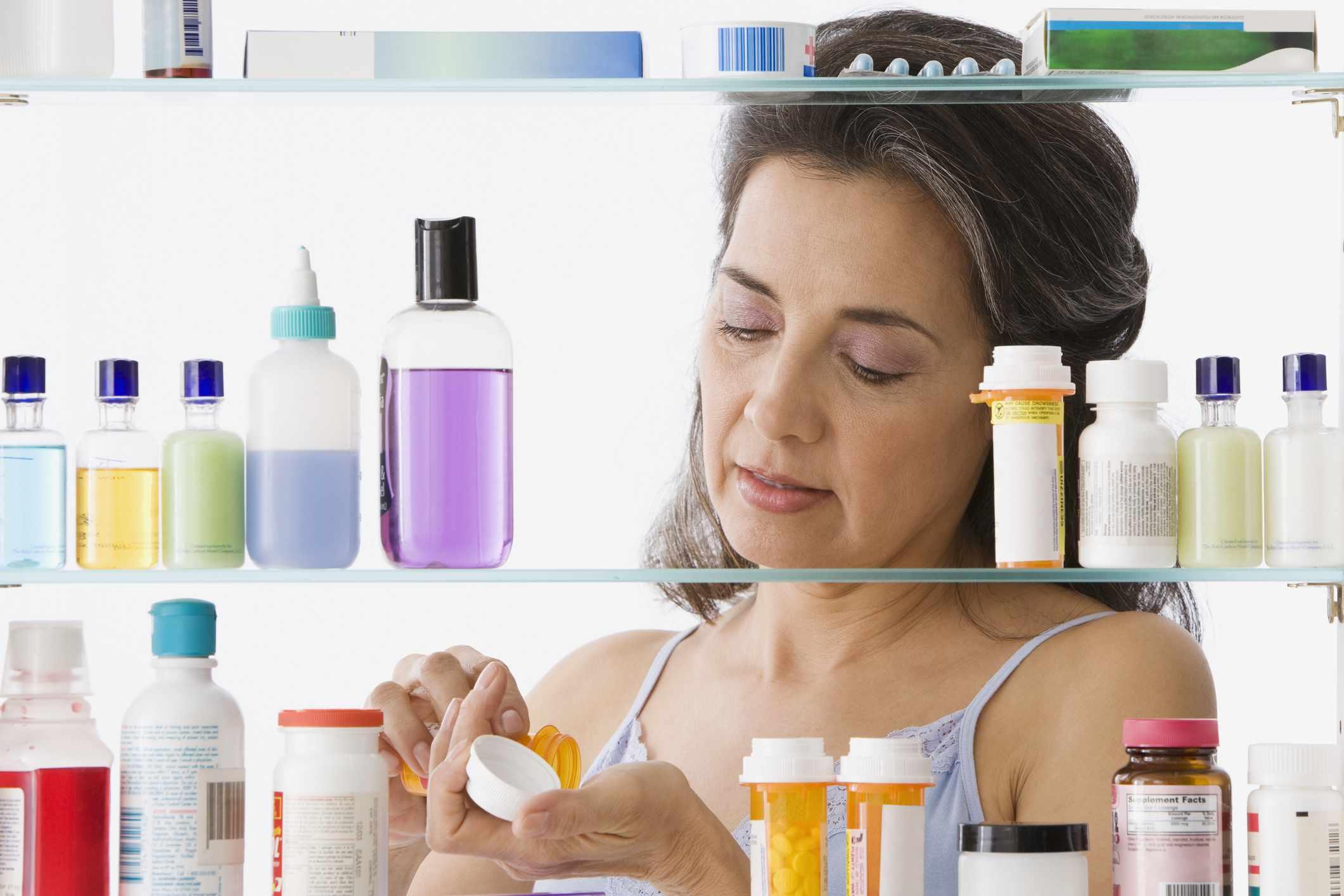 woman taking medication in bathroom