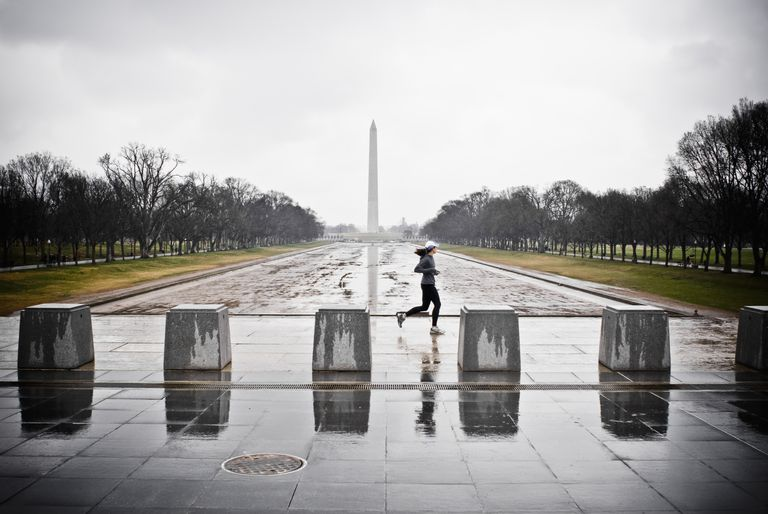 A female runner by the empty reflecting pool by the Lincoln Memorial